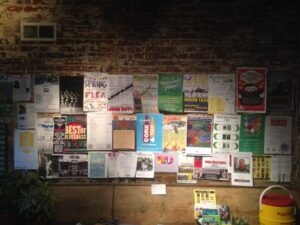 Bulletin board at 3rd Street Stuff Coffee Shop, crowded with posters touting current events